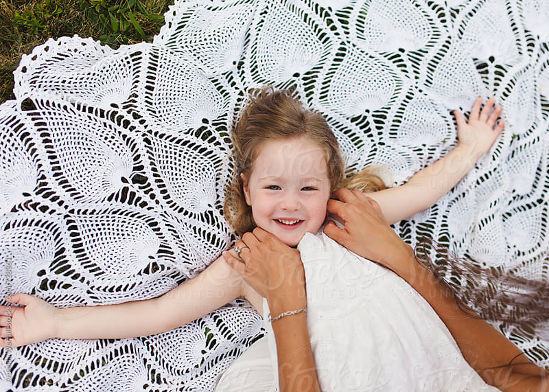 Portrait of a smiling young girl on lace blanket, tickled by mother by Amanda Worrall for Stocksy United