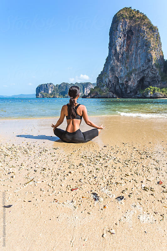 Young woman doing yoga alone on a tropical beach by Soren Egeberg for Stocksy United