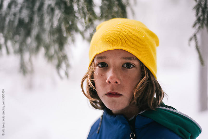 Young boy portrait in the snowy woods by Boris Jovanovic for Stocksy United