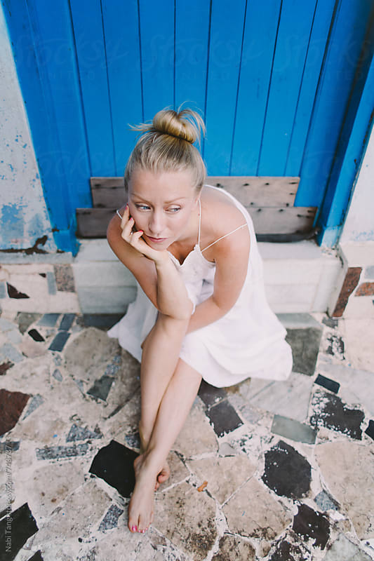 Beautiful blond woman sitting in front of bright blue door of the beach house by Nabi Tang for Stocksy United