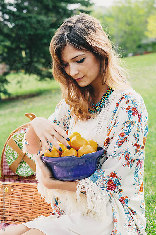 Woman with a bowl of oranges picnicking outdoors by Ania Boniecka for Stocksy United