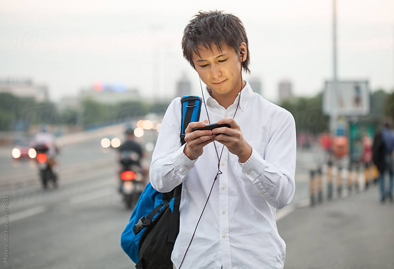 Young Asian Man Using Phone by Mosuno for Stocksy United