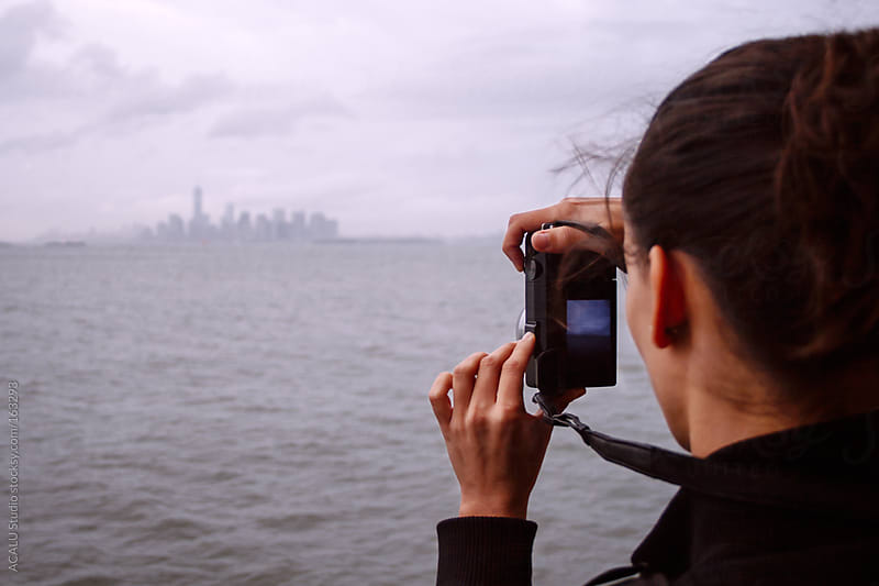 Woman photographing the Manhattan Skyline by ACALU Studio for Stocksy United