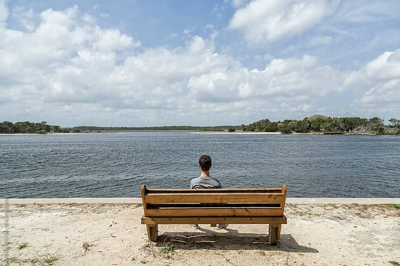 Teenage boy sitting on a wood bench looking out the water by Adam Nixon for Stocksy United