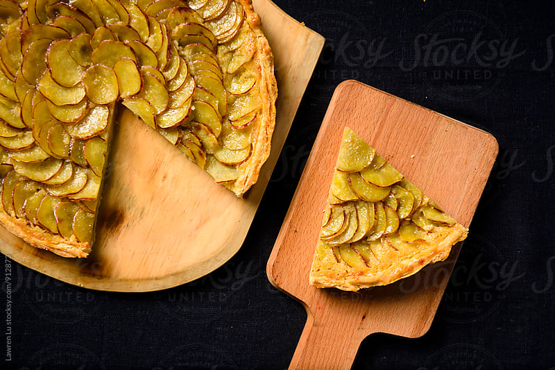 baked sliced sweet potatoes pie on wooden boards by Lawren Lu for Stocksy United