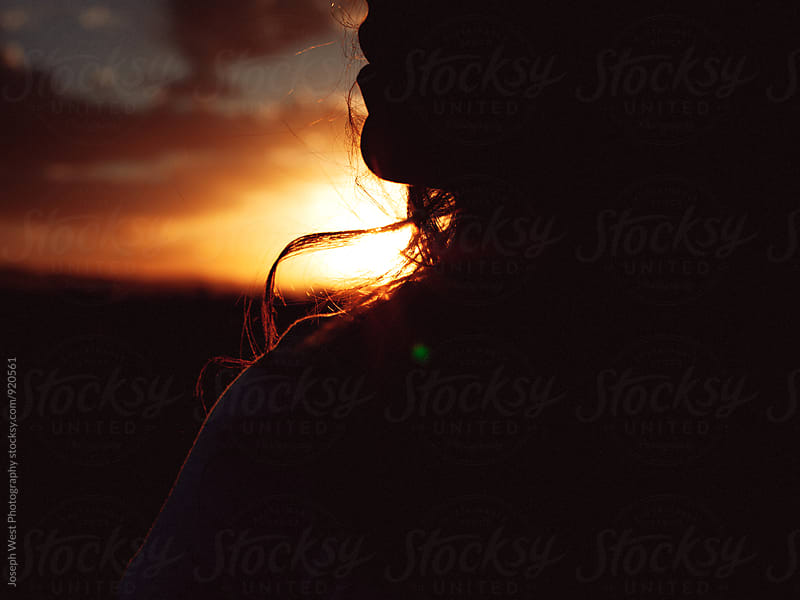 Closeup profile of a woman against the sunset by Joseph West Photography for Stocksy United