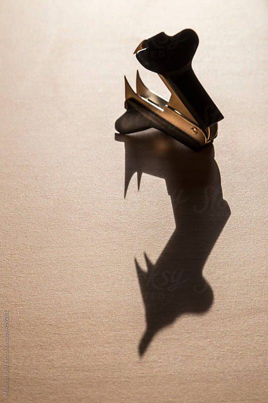 Staple remover casting a long shadow on a desk by Melanie Kintz for Stocksy United