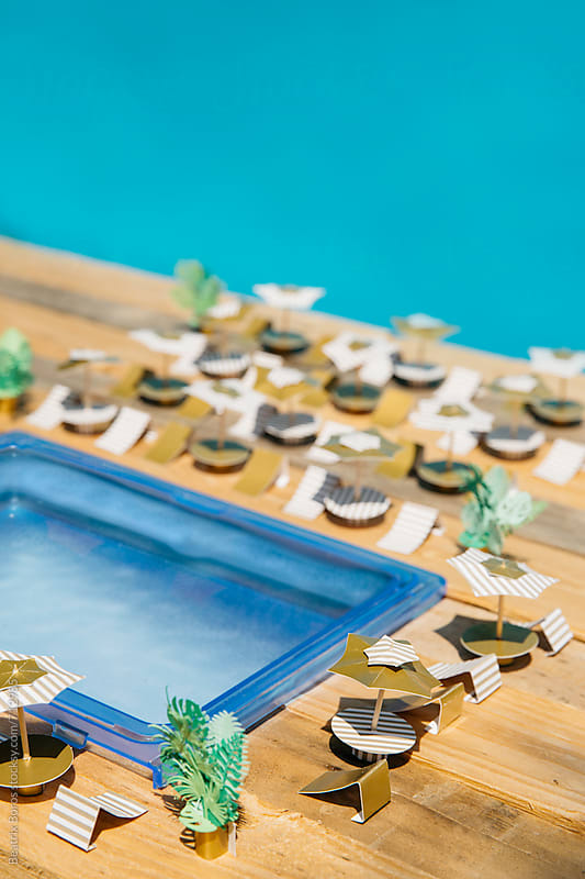 Detail of a miniature pool with umbrellas and beach chairs made of paper by Beatrix Boros for Stocksy United