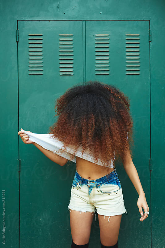 Photo of young Afro-American woman showing her slim stomach by Guille Faingold for Stocksy United