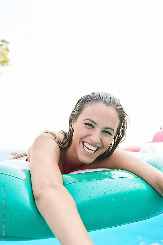 Laughing blondie with wet hair on air mattress by Guille Faingold for Stocksy United