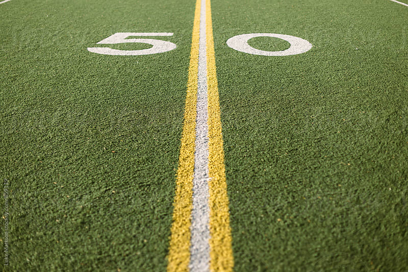 Fifty Yard Line Marked On Turf Football Field by Luke Mattson for Stocksy United