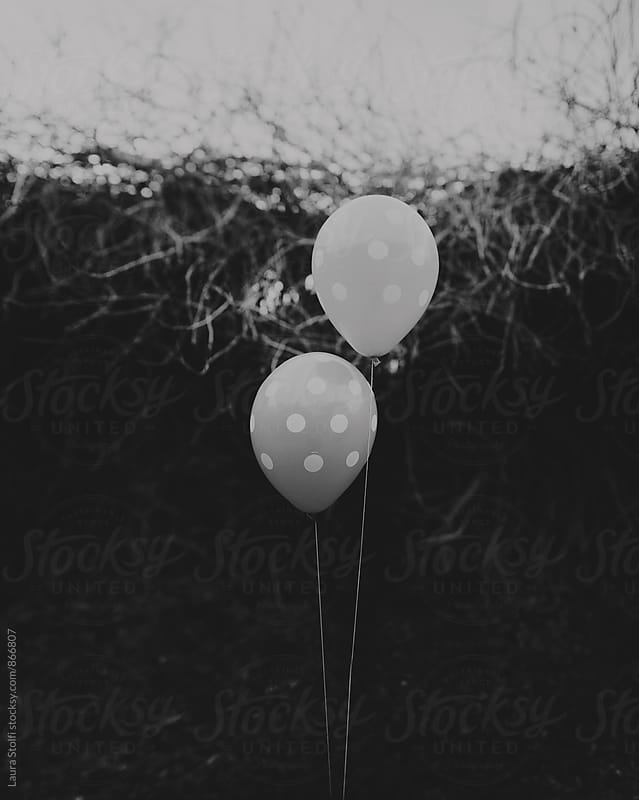 Polka dot balloons floating outdoors in black and white by Laura Stolfi for Stocksy United