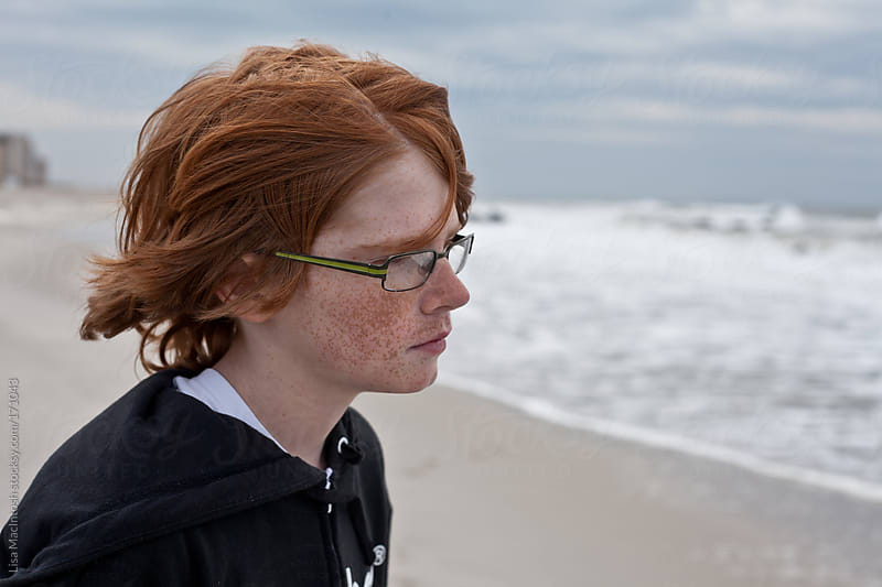 red headed staring out at the sea with wind blown hair wearing glasses by Lisa MacIntosh for Stocksy United