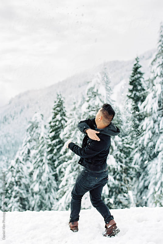 Young man throwing snow by Daniel Kim Photography for Stocksy United