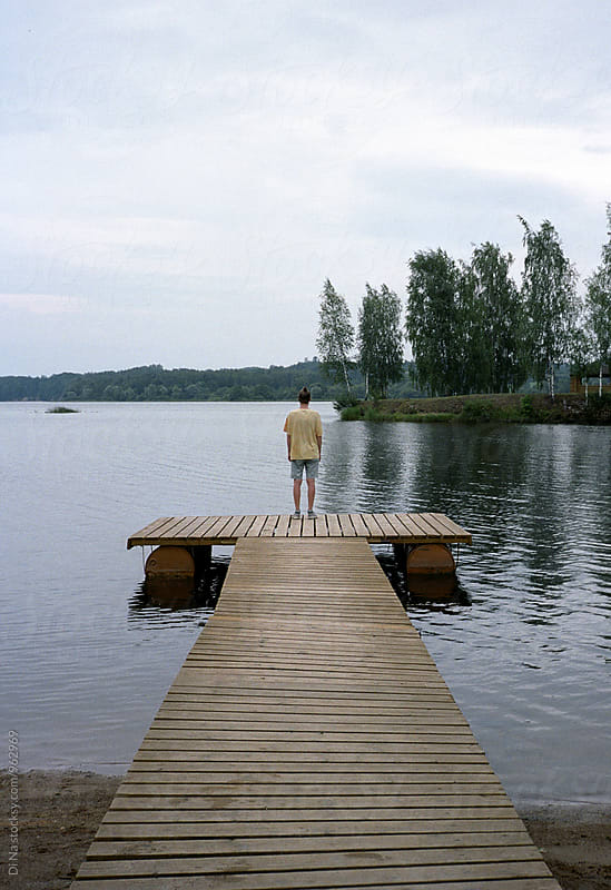 Young man at dock near river by Dina Lun for Stocksy United