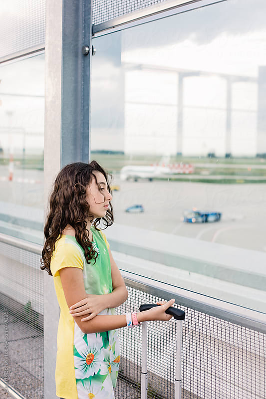 Vertical photo of a girl who is watching the planes at the airport while waiting by Beatrix Boros for Stocksy United