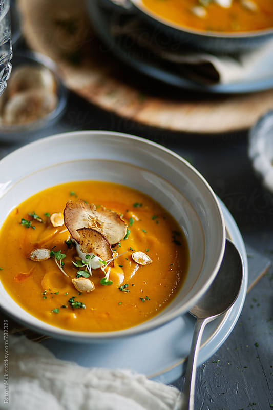A bowl of butternut squash soup on a table. by Darren Muir for Stocksy United