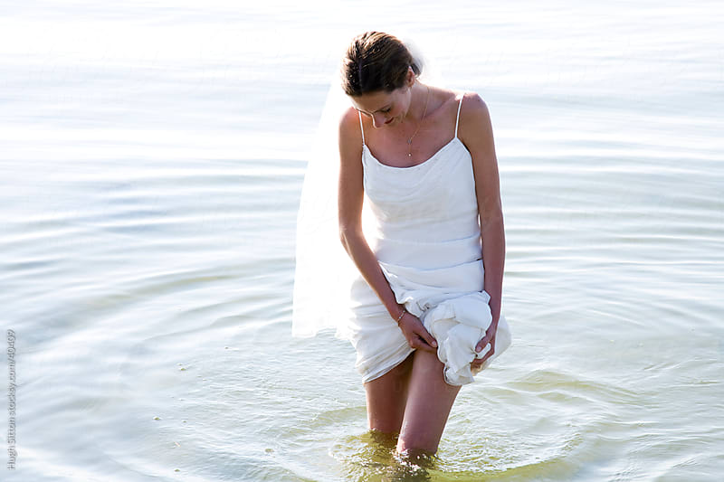 Bride standing in the sea. by Hugh Sitton for Stocksy United
