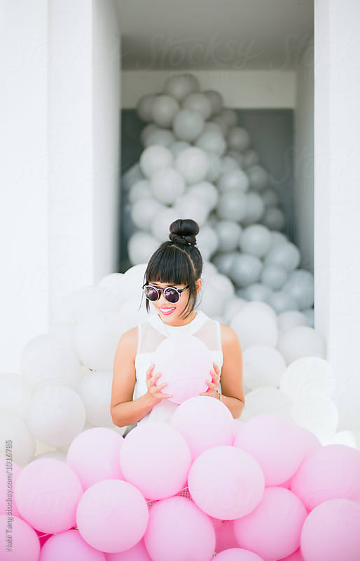 Beautiful woman standing with too many white and pink balloons by Nabi Tang for Stocksy United