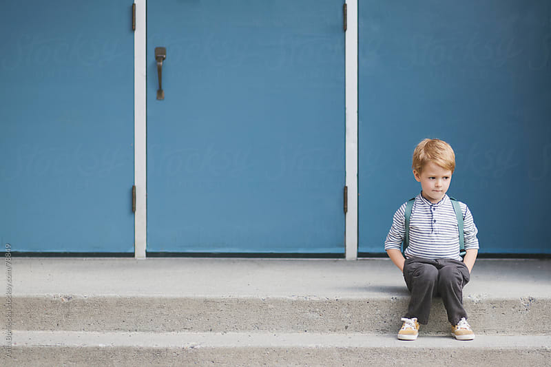 An anxious blonde boy sitting on the steps of a school on his first day of school by Ania Boniecka for Stocksy United