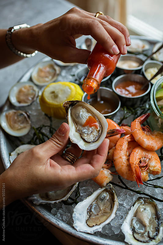Shellfish Platter with oyster and hot sauce by Andrew Cebulka for Stocksy United