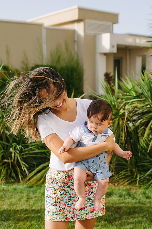 Beautiful windswept woman carrying young child in front of an apartment building. by Julia Forsman for Stocksy United