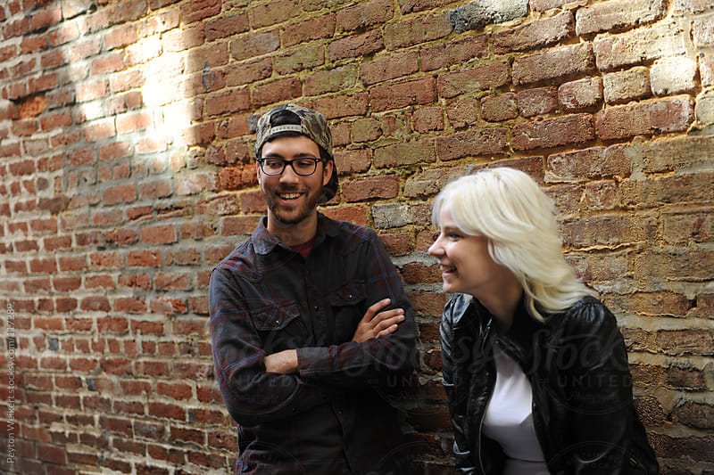 Hip Young Man and Woman Hang Out and Laugh Against a Plain Brick Wall by Peyton Weikert for Stocksy United