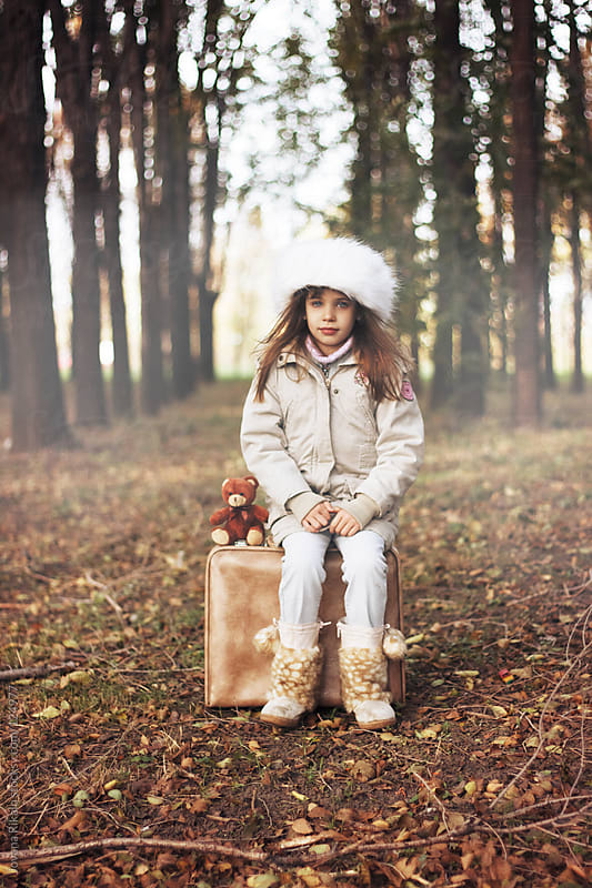 Cute little girl sitting on a suitcase in nature  by Jovana Rikalo for Stocksy United