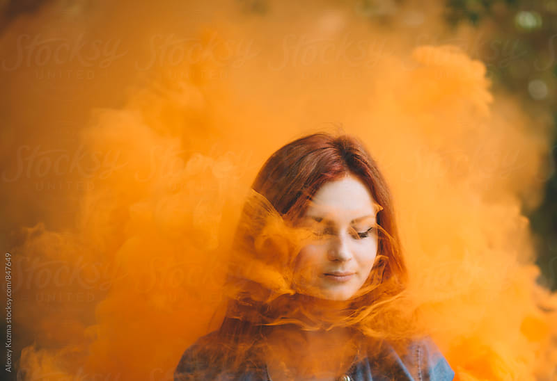 portrait of  young woman with smoke bomb by Alexey Kuzma for Stocksy United