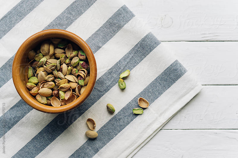 dry pistachios in the plate by Javier Pardina for Stocksy United