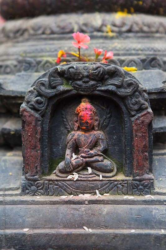 Small stone sculpture of Buddha covered in vermillion powder, Nepal. by Shikhar Bhattarai for Stocksy United