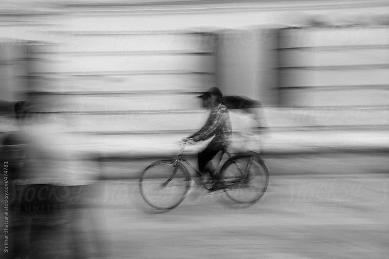 A cyclist speeding off in a street. by Shikhar Bhattarai for Stocksy United