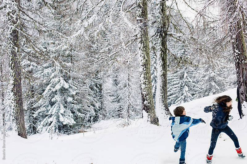 Siblings snowball fighting in the nature in Winter by Beatrix Boros for Stocksy United