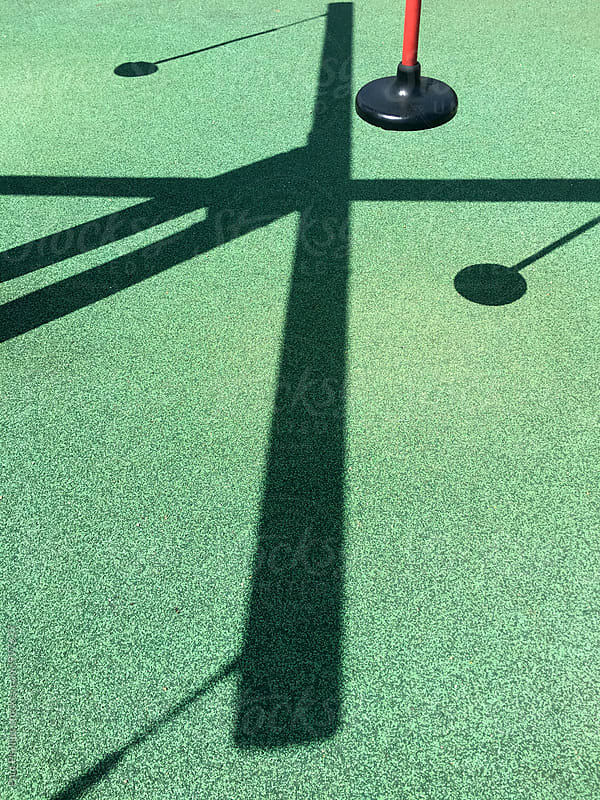Strong shadows on a children's playground. Formed from a round seat with timber moving parts. by Paul Phillips for Stocksy United