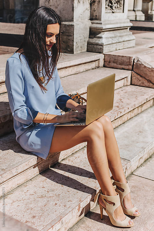Businesswoman in a Blue Dress Using her Laptop by Lumina for Stocksy United
