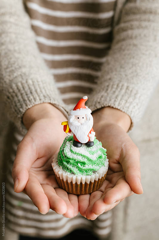 Woman holding christmas cupcake by MaaHoo Studio for Stocksy United