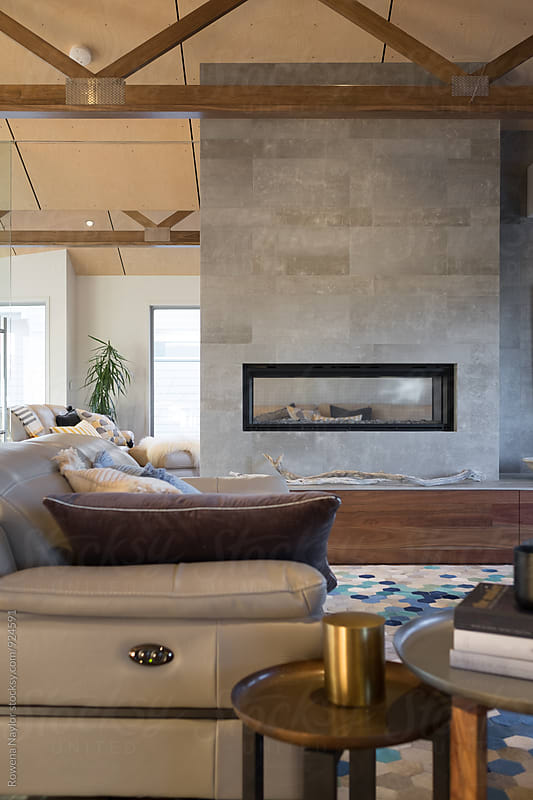 Luxurious lounge room with fireplace by Rowena Naylor for Stocksy United