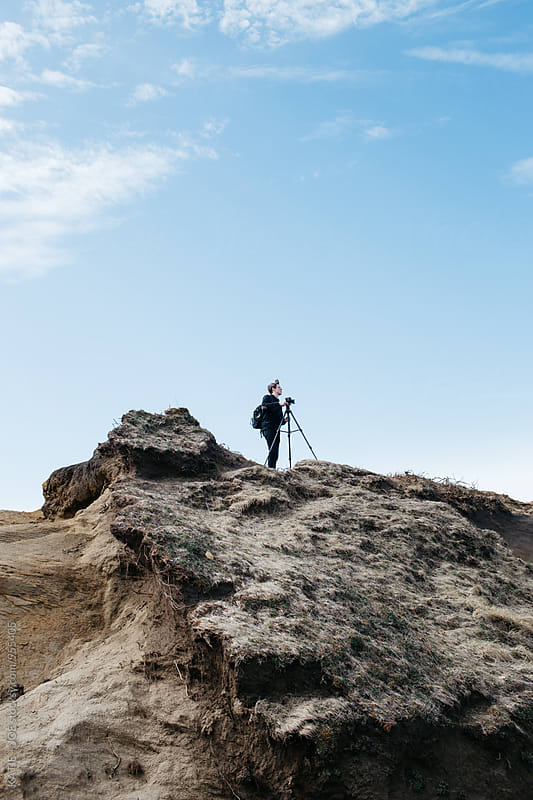 Man standing high on a rock with a tripod by KATIE + JOE for Stocksy United