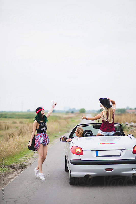 Group of happy female friends enjoying road trip in their cabriolet by Jovana Rikalo for Stocksy United
