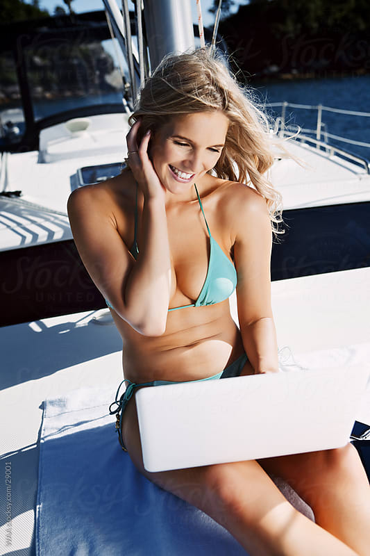 Attractive woman in bikini working with laptop on boat by WAA for Stocksy United