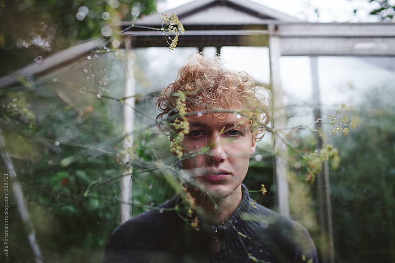 Beautiful male model in green house by Julia Forsman for Stocksy United