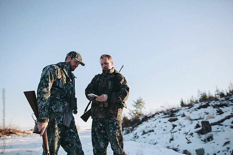 Two men hunting together using gps technology map on mobile phone by Rob and Julia Campbell for Stocksy United