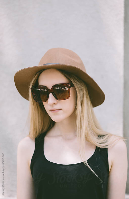 portrait of young woman with hat and sunglasses by Alexey Kuzma for Stocksy United