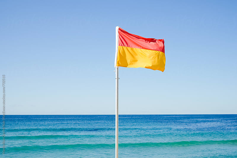 A lifeguards flag on a bright sunny day by Maximilian Guy McNair MacEwan for Stocksy United