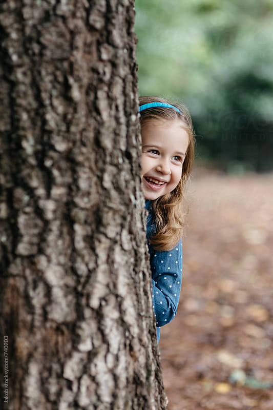 Beautiful young girl peeking out from behind a tree by Jakob for Stocksy United