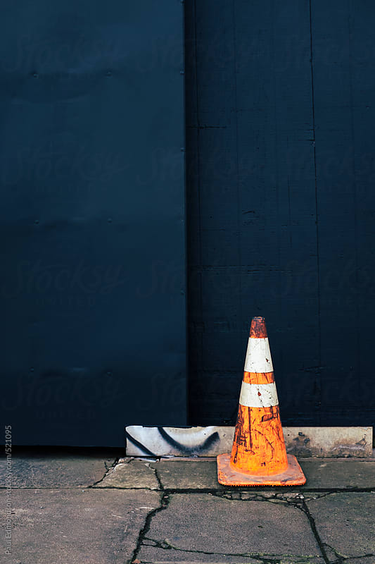 Traffic cone on cracked urban sidewalk, painted wall in background by Paul Edmondson for Stocksy United
