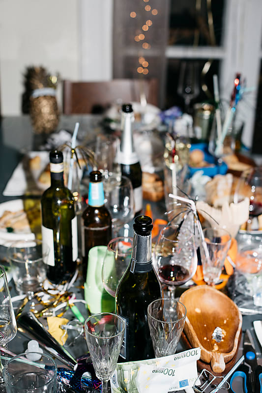 Messy cluttered table after a New Year's Eve party by Beatrix Boros for Stocksy United