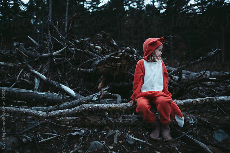 Child in fox costume sitting in front clearcut log pile by Rob and Julia Campbell for Stocksy United
