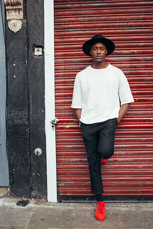 Outdoor Portrait of Young Stylish Black Man With Hat Leaning Against Red Rolling Shutter by VISUALSPECTRUM for Stocksy United