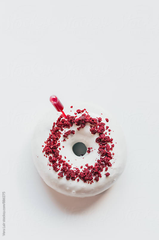 White donut with red crusty by Vera Lair for Stocksy United